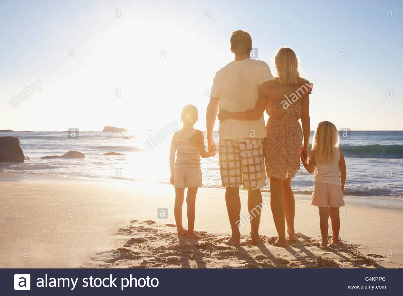 Family on beach holding hands - Stock Image