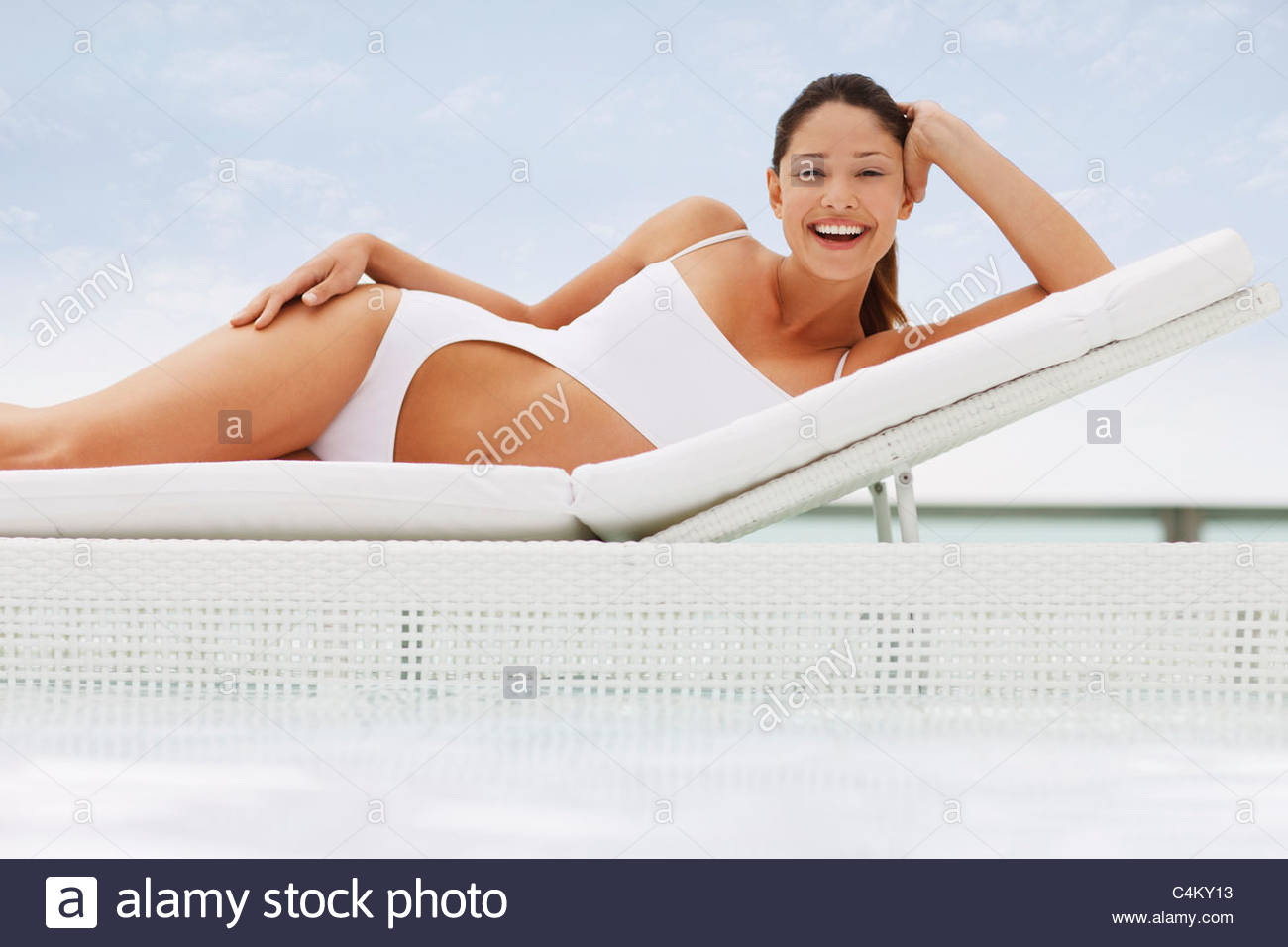 Woman in bathing suit laying on lounge chair at poolside - Stock Image