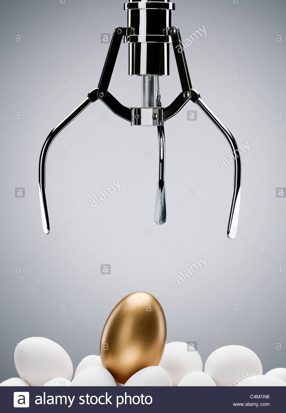 Mechanical claw reaching for golden egg - Stock Image