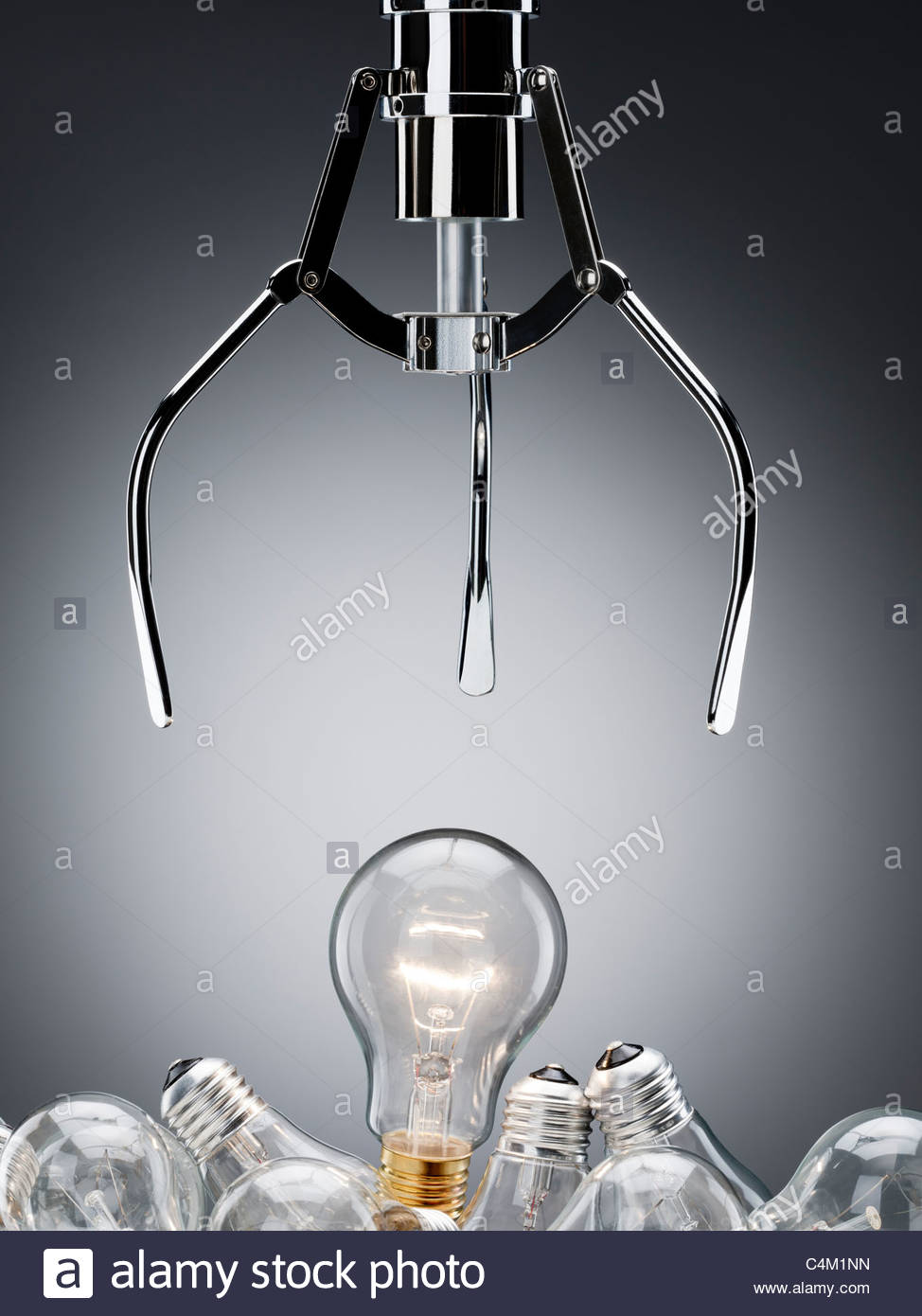 Mechanical claw reaching for light bulb - Stock Image