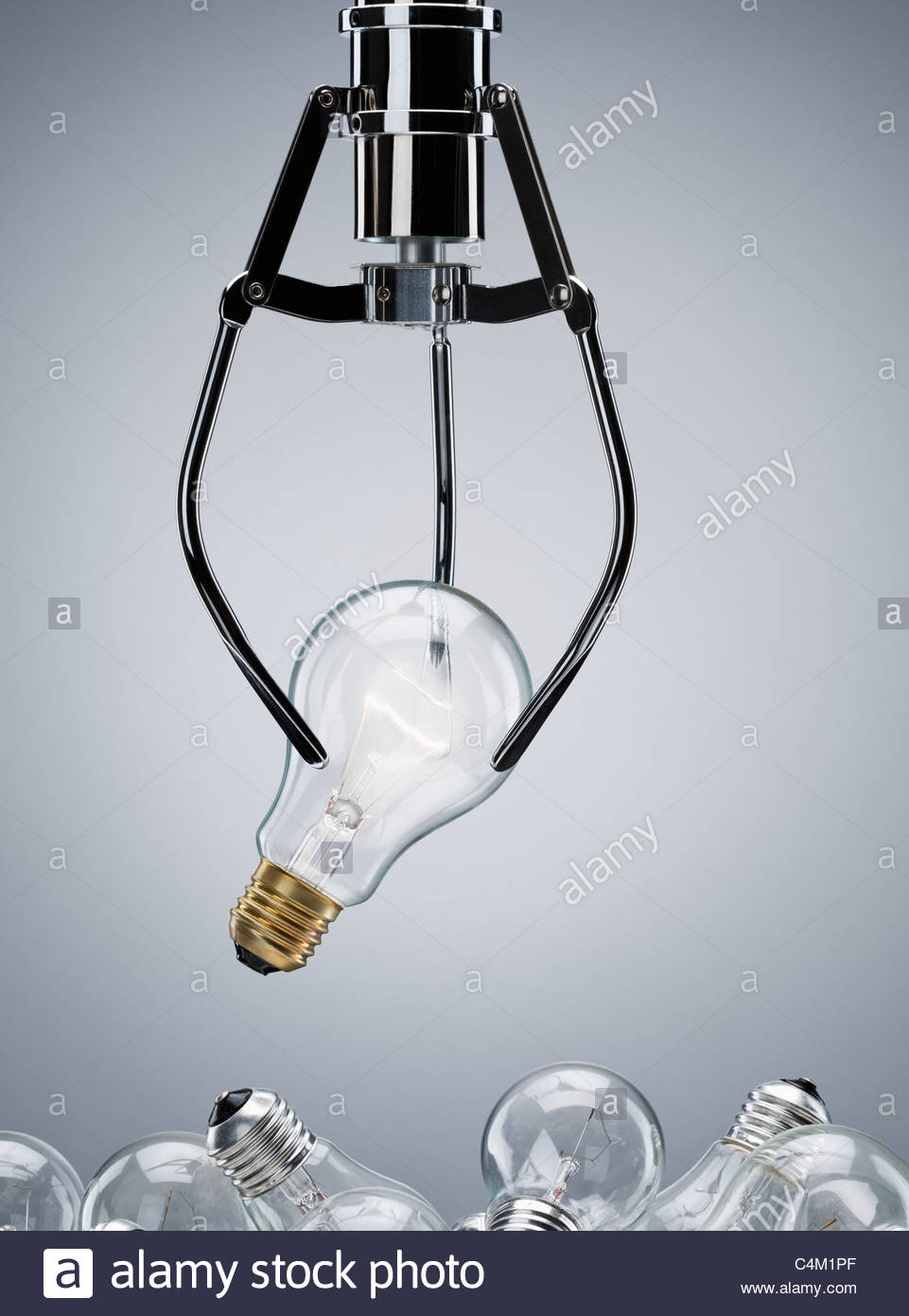 Mechanical claw lifting light bulb - Stock Image