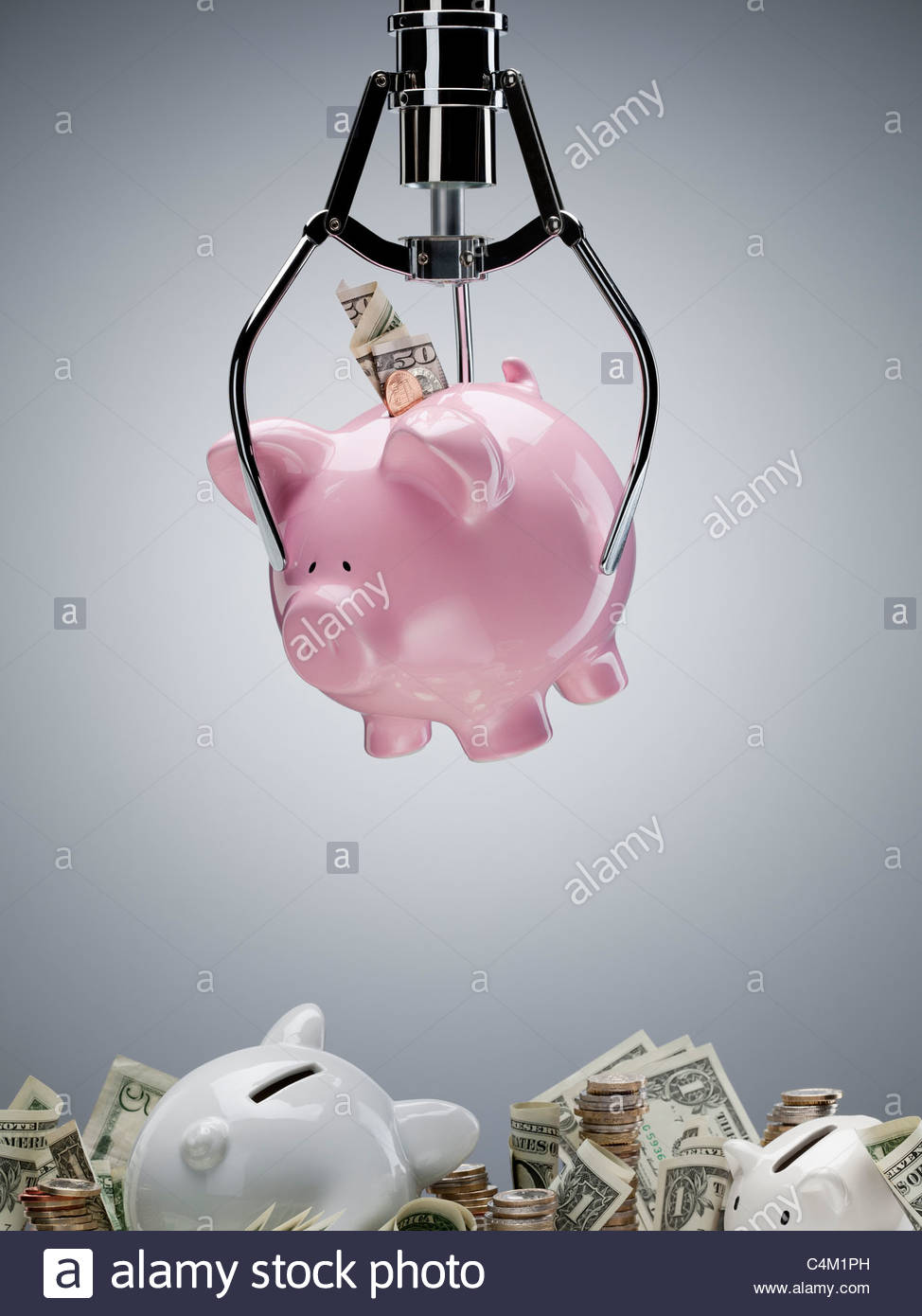 Mechanical claw lifting piggy bank - Stock Image