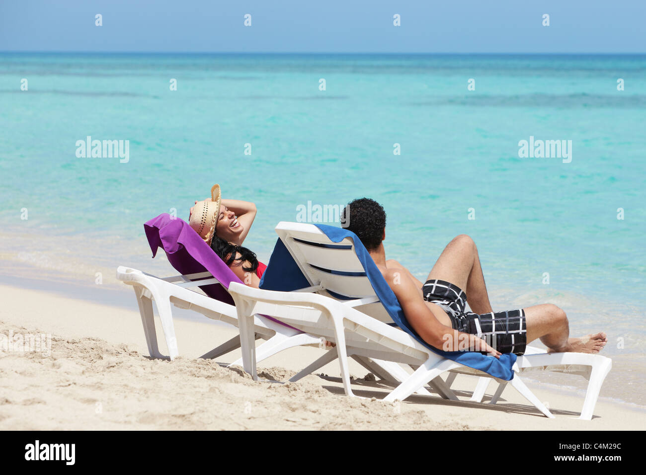 husband and wife relaxing on sunbeds on the beach and smiling. Horizontal shape, side view, copy space - Stock Image