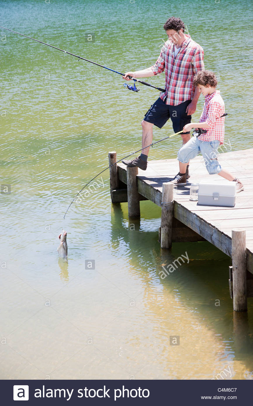 Father and son fishing off dock - Stock Image
