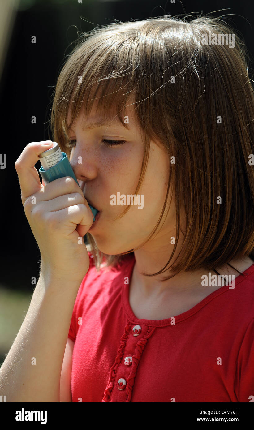 Young Asthma patient using an inhaler Stock Photo