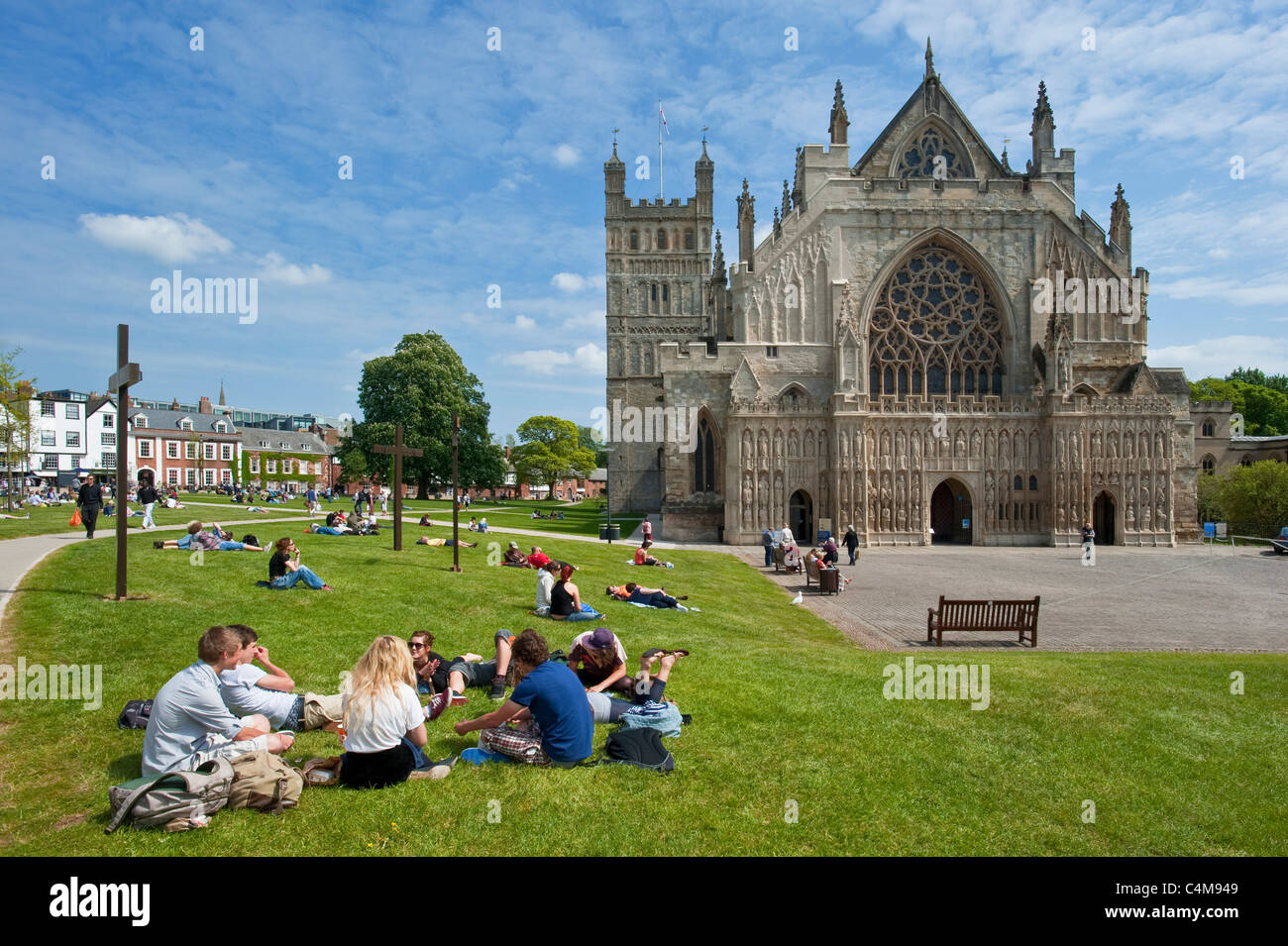The famous West Window of Exeter Cathedral with students relaxing on the grass of Cathedral Green. - Stock Image