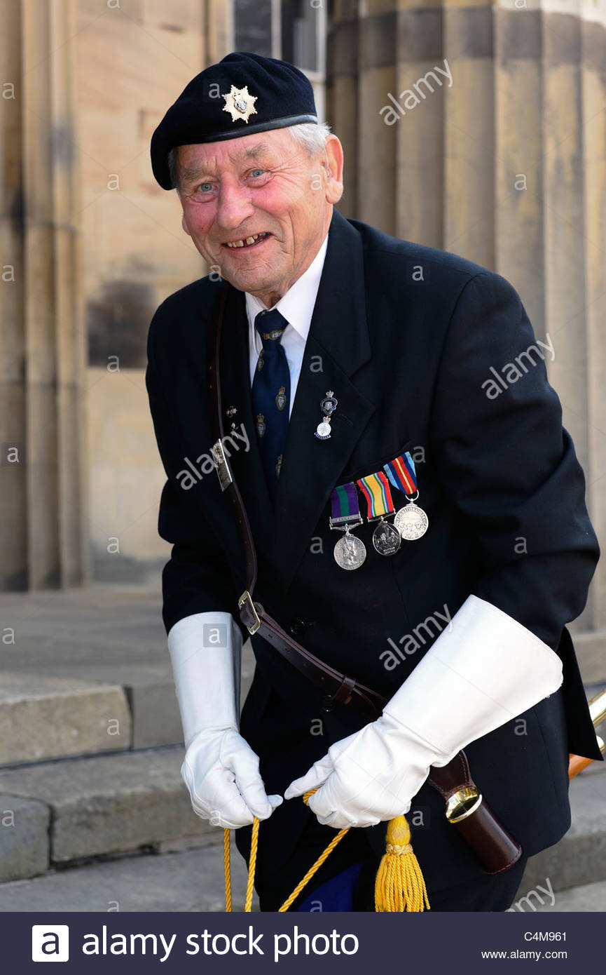 Royal British Legion ex serviceman outside the Shire hall, Hereford City, UK. Veteran soldier putting away flag - Stock Image