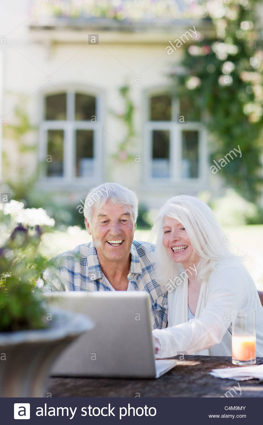 Senior couple using laptop at table in garden - Stock Image
