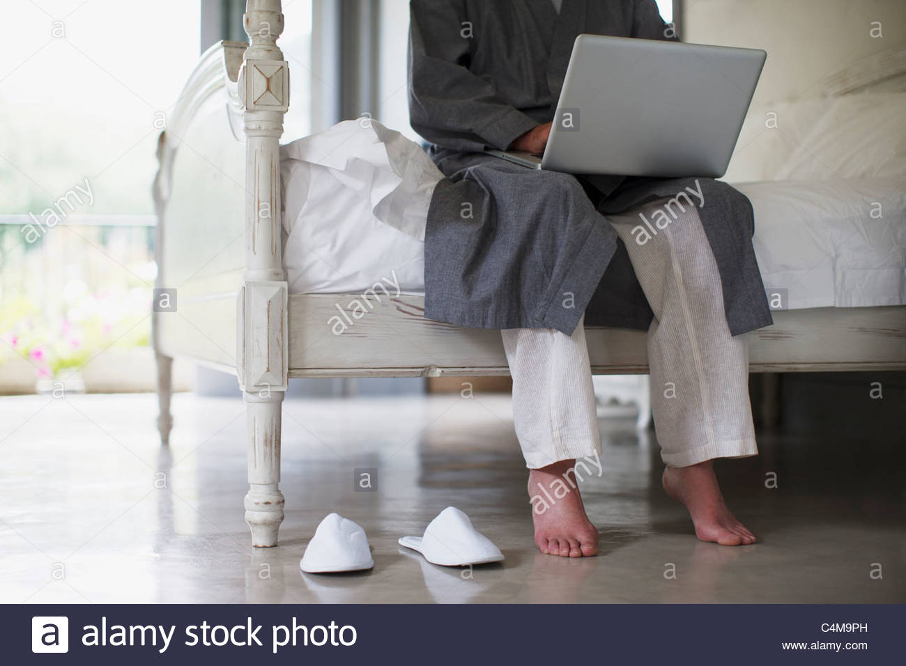 Senior man with bare feet sitting on edge of bed using laptop - Stock Image