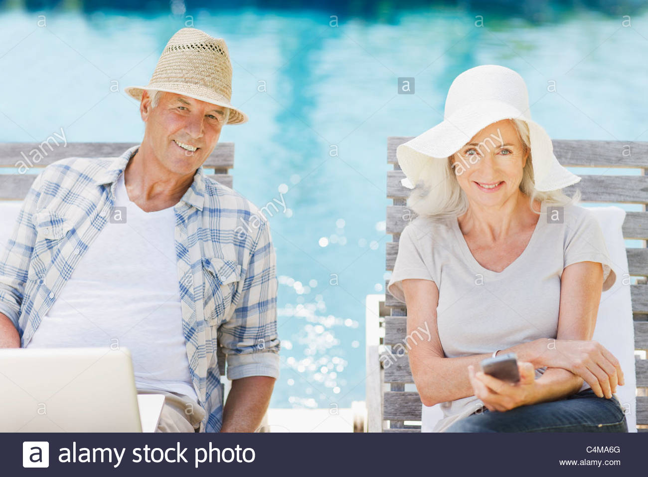Senior couple using laptop and cell phone at poolside - Stock Image