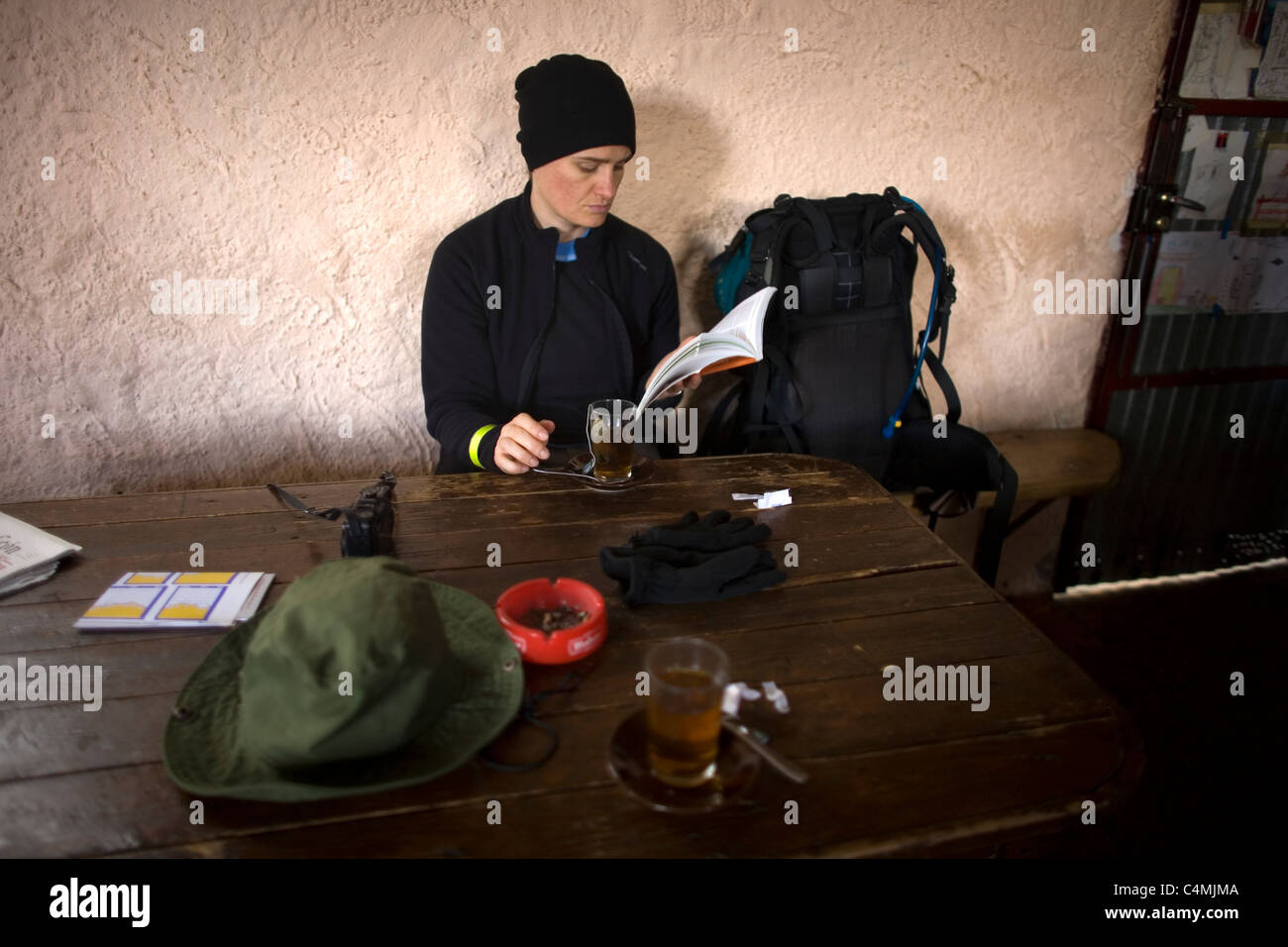 A pilgrim checks her tourist guide in a bar in the French Way of the Way of Saint James, in El Ganso, Spain - Stock Image