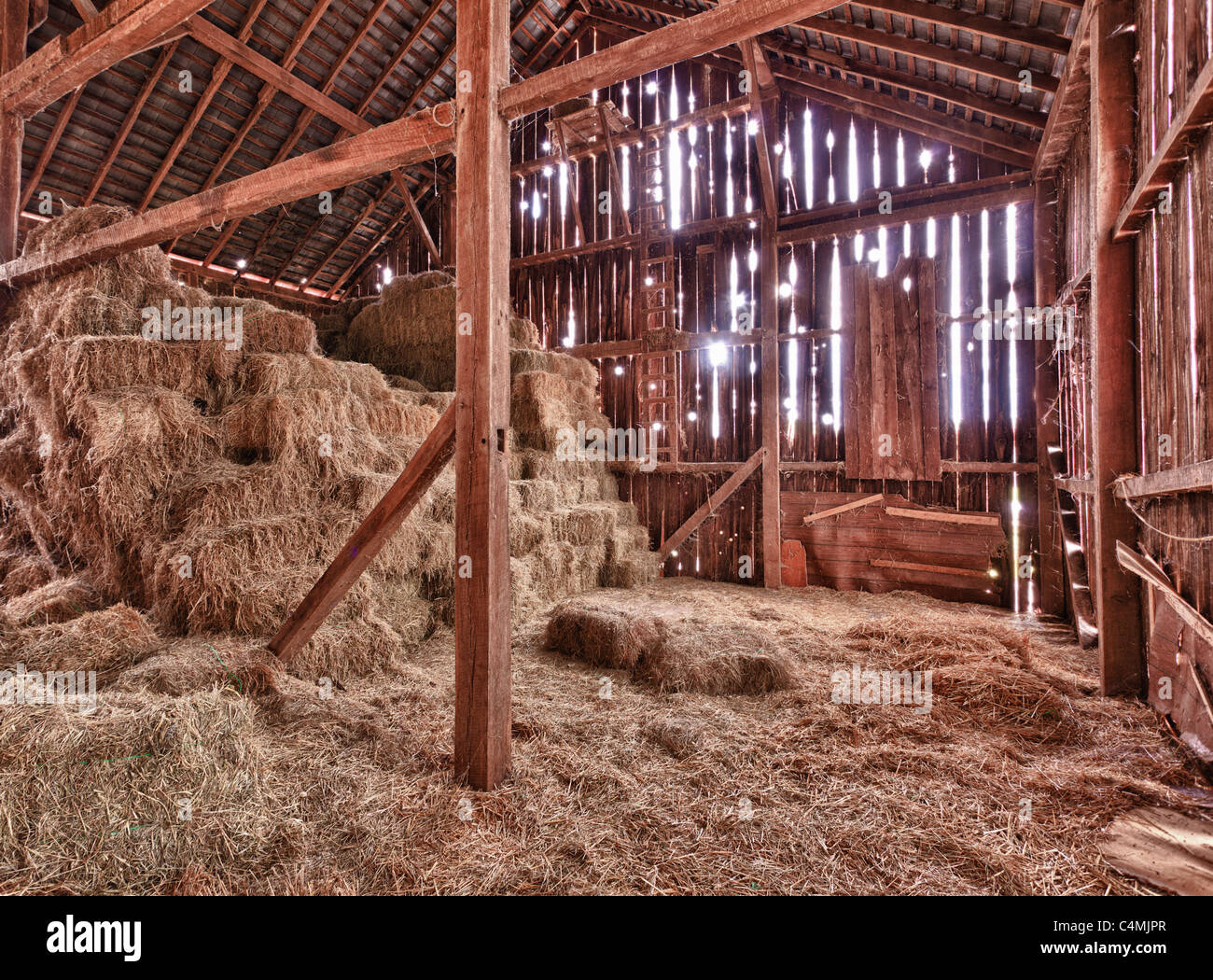 Old Barn with the sun streaming from outside and straw and hay on the floor of the hayloft - Stock Image