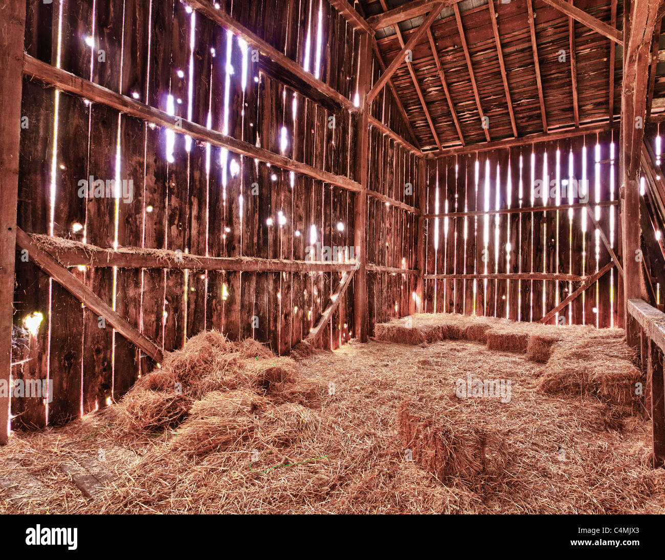 Old Barn with the sun streaming from outside and straw and hay on the floor of the hayloft, USA - Stock Image