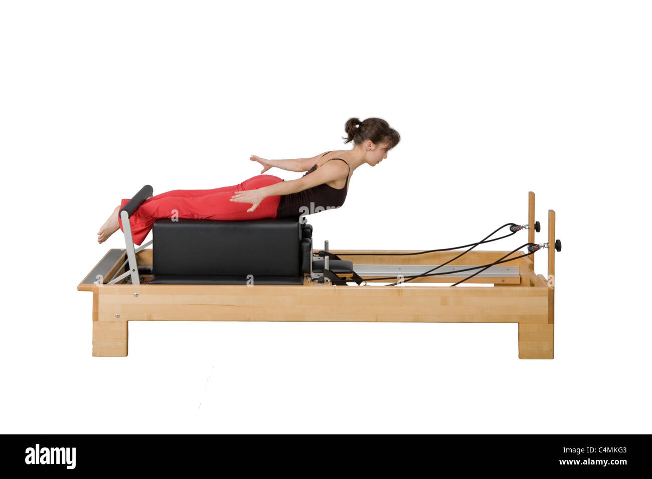 Young woman doing Pilates exercises on the Reformer - Stock Image
