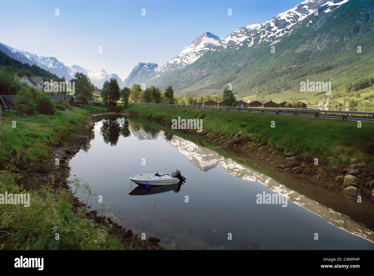 Small Lake and boat with snowcapped mountains at  Stryn, Olden, Norway - Stock Image