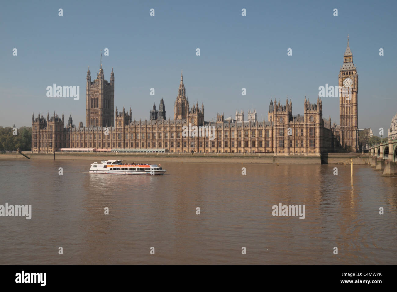 The Palace of Westminster (Houses of Parliament),  Elizabeth Tower (Big Ben) and River Thames cruise boat in London - Stock Image