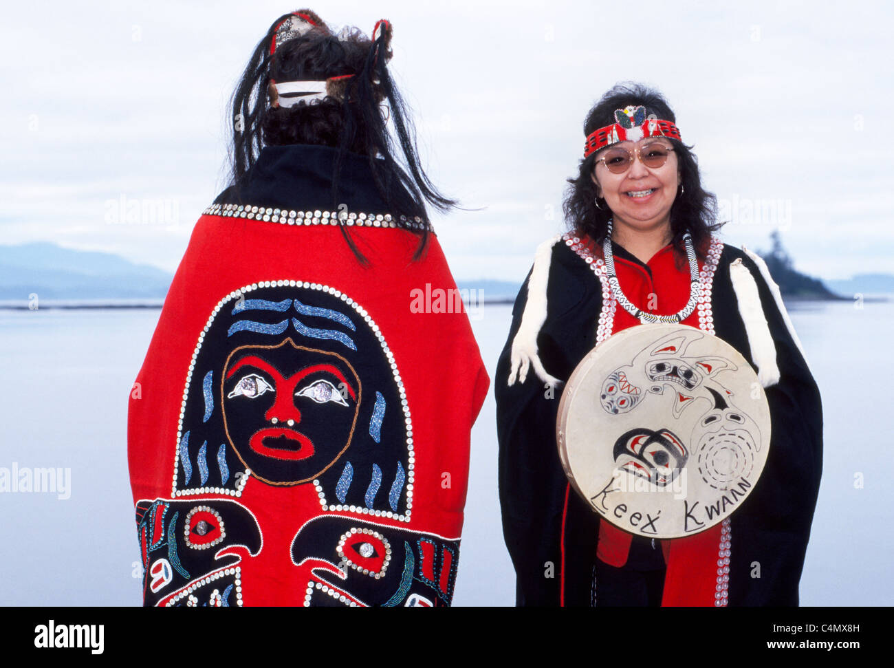Two Tlingit Native American women display traditional capes designed with buttons and a drum of the Keex tribe (kwaan) - Stock Image