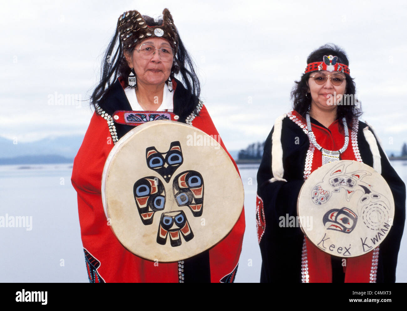 Two Tlingit Native American women display traditional capes designed with buttons and drums of the Keex tribe (kwaan) - Stock Image