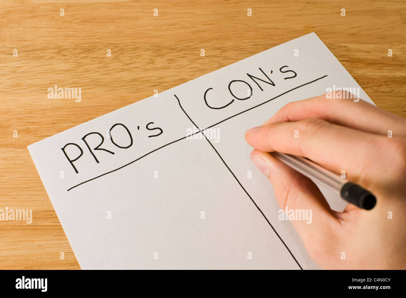 Business man weighing up the pro's and con's of a decision - Stock Image