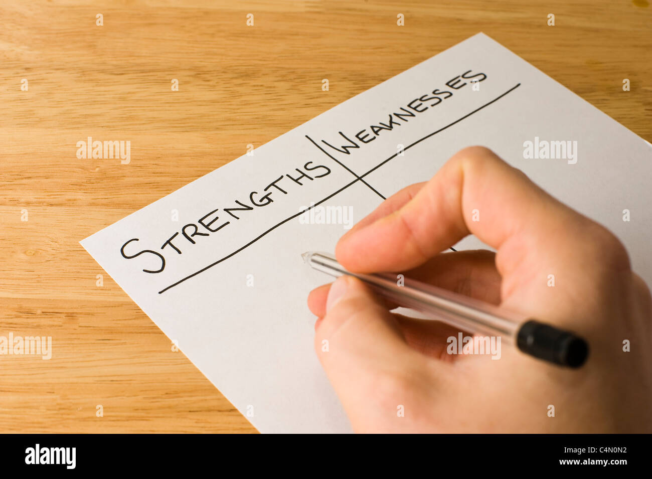 Business man writing a list weighing up the strengths and weaknesses of a business - Stock Image