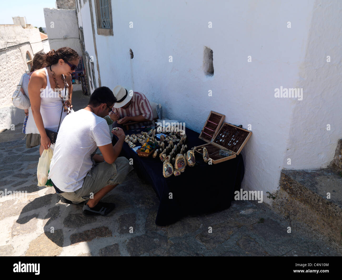 Chora Patmos Greece People Looking At Stall Selling Religious Artefacts And Jewellery In Narrow Street - Stock Image