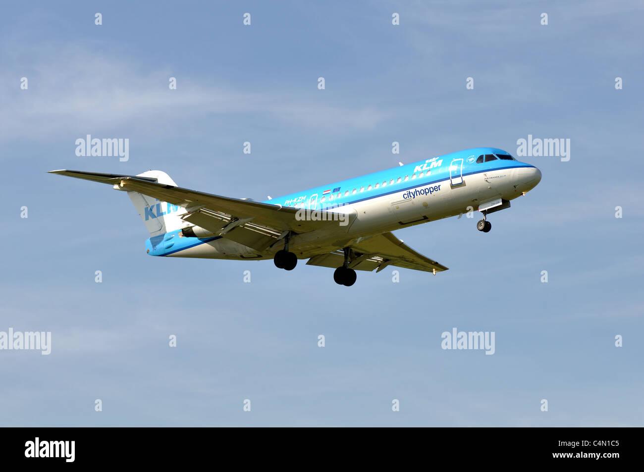 KLM Cityhopper Fokker 70 aircraft approaching Birmingham Airport, UK - Stock Image