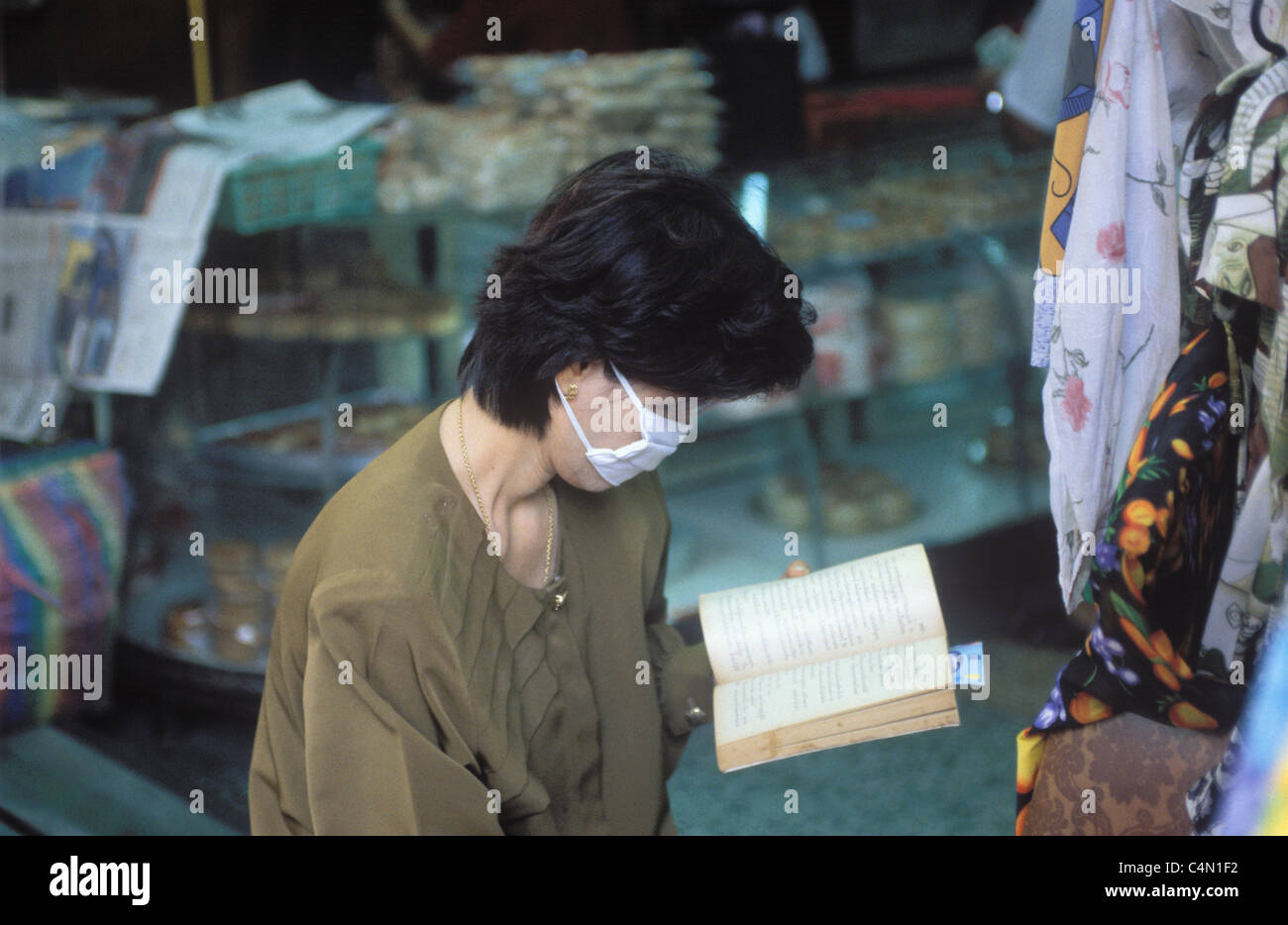 thai woman trader, wearing an anti-pollution mask, reading a book in a bangkok shop - Stock Image