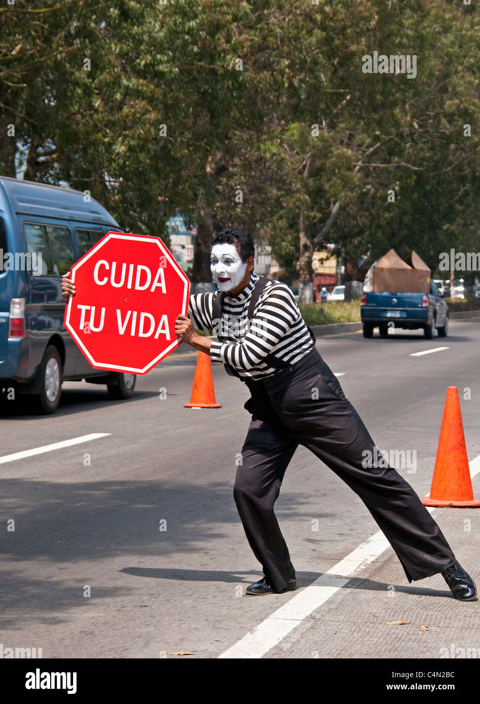 Mime on Guatemala City street with 'Take Care of Your Life' (Cuida tu Vida) sign promoting highway safety. - Stock Image