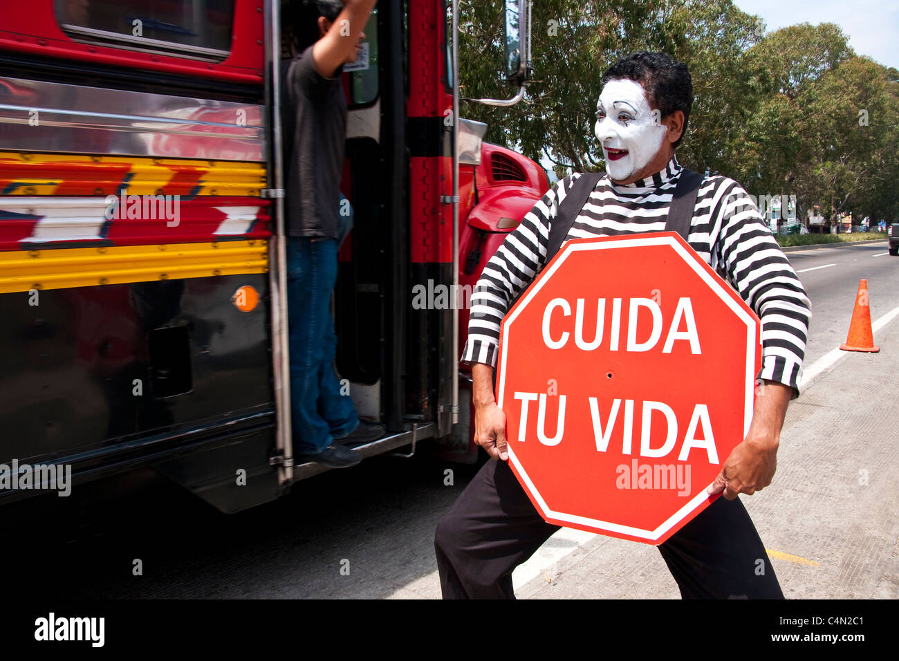Mime on Guatemala City street with 'Take Care of Your Life' (Cuida tu Vida) sign promoting highway safety - Stock Image