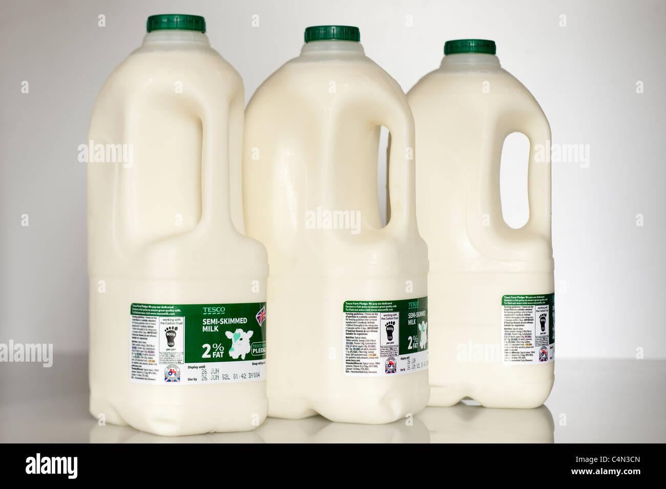 Three plastic four pint or 2.272 litre bottles of Tesco semi skimmed milk - Stock Image