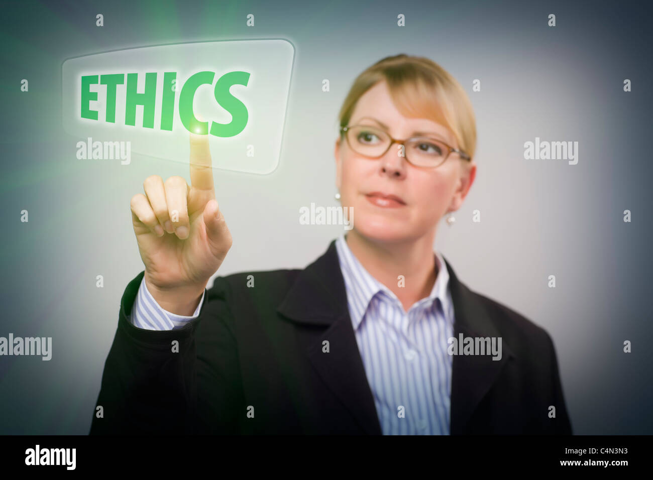 Attractive Blonde Businesswoman Pushing Ethics Button on an Interactive Touch Screen. - Stock Image