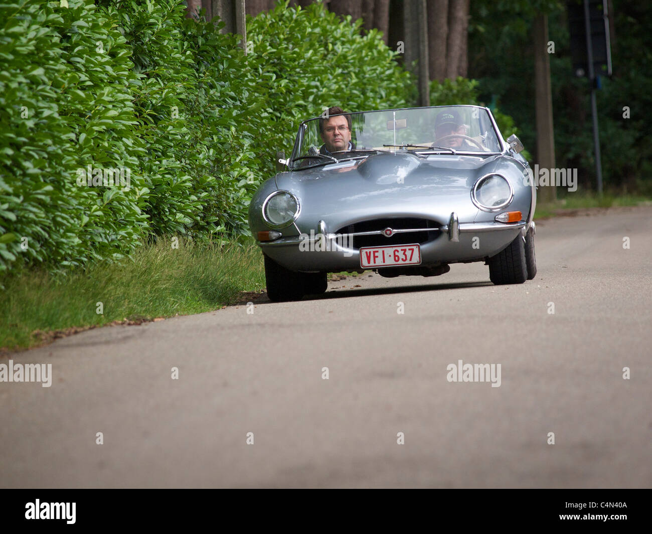 Silver grey Jaguar E-type participating in a classic car rallye in Belgium - Stock Image