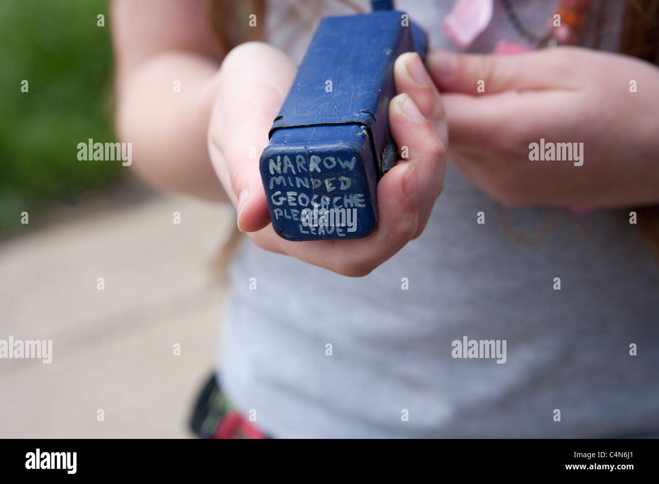 Child holding a micro-cache - Stock Image