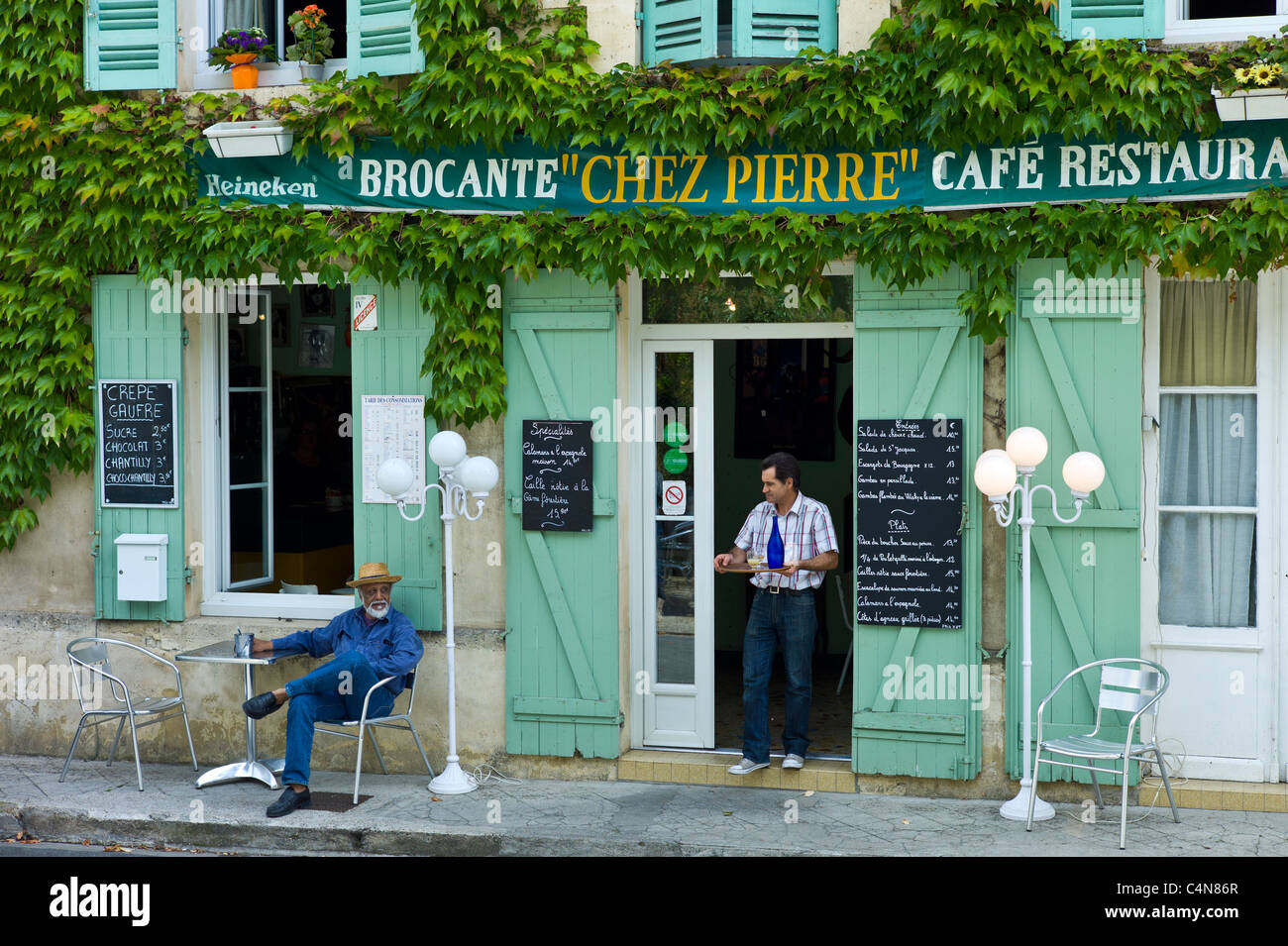 Waiter serves customer Pastis at traditional French Cafe Chez Pierre in Castelmoron d'Albret in Bordeaux region, - Stock Image