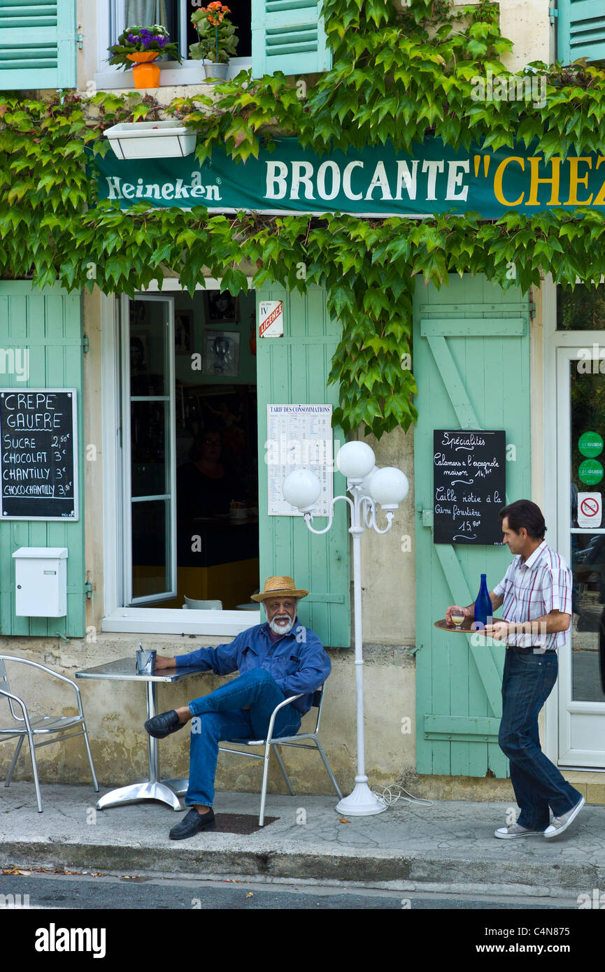 Waiter serves customer Pastis at traditional French Cafe in town of Castelmoron d'Albret in Bordeaux region, - Stock Image