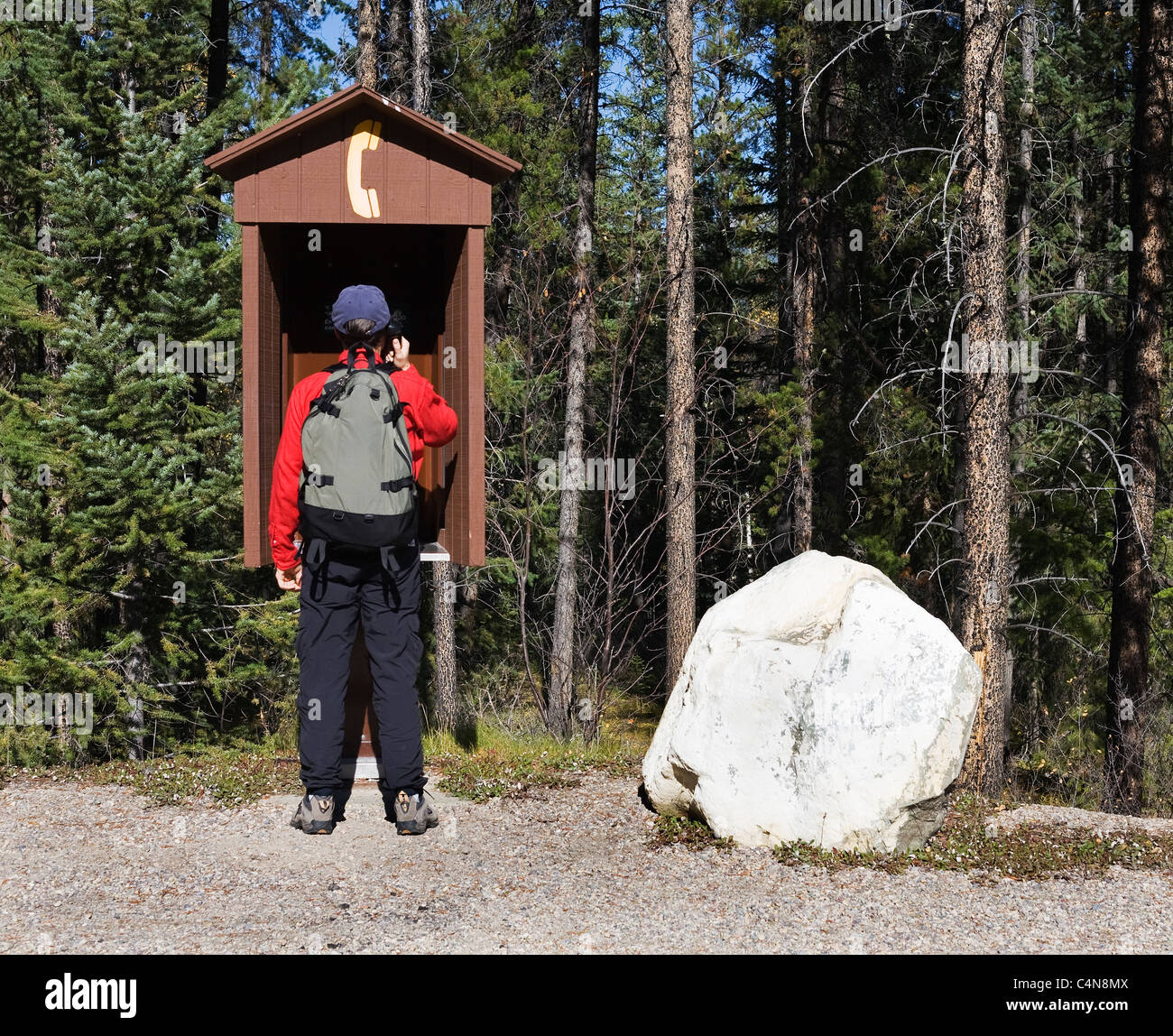 Hiker calling on outdoor pay phone, Jasper National Park, Alberta, Canada. - Stock Image