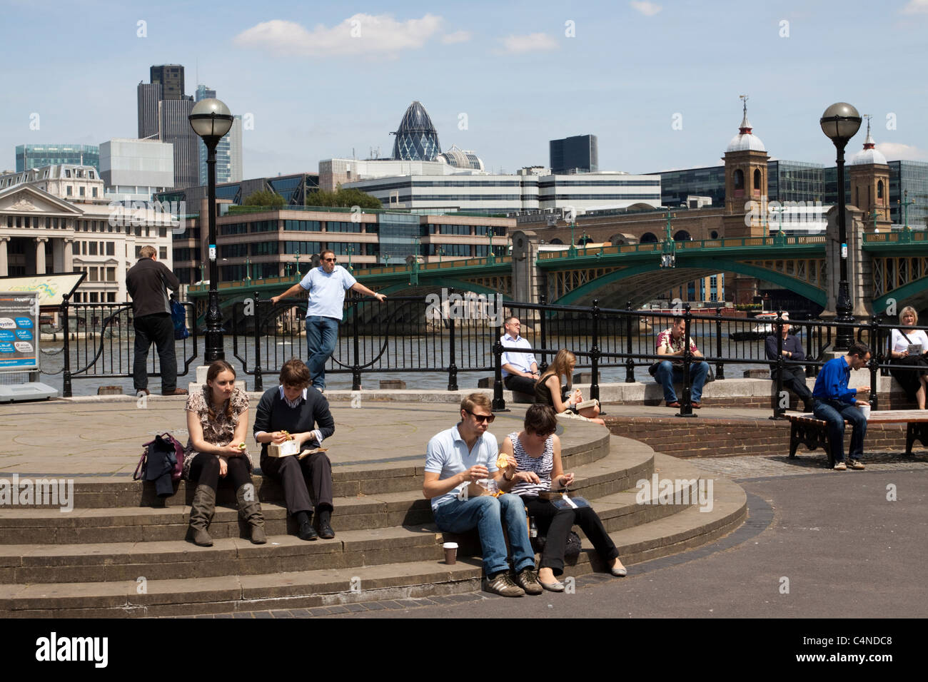 People eating lunch on the steps of Bankside Pier, London, England, UK - Stock Image