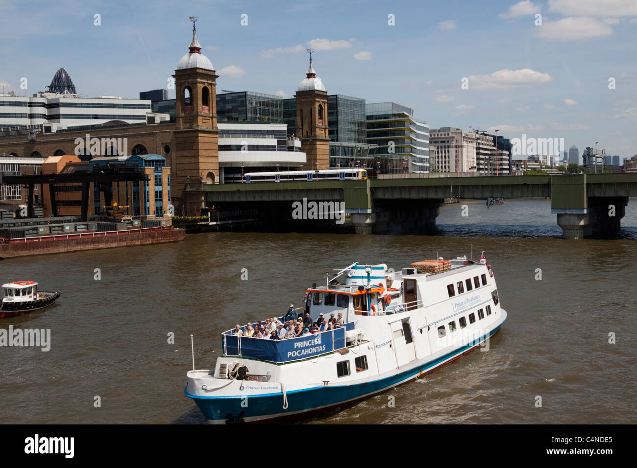 Tourist boat on the River Thames with Cannon street train station in the background, London, England, UK - Stock Image
