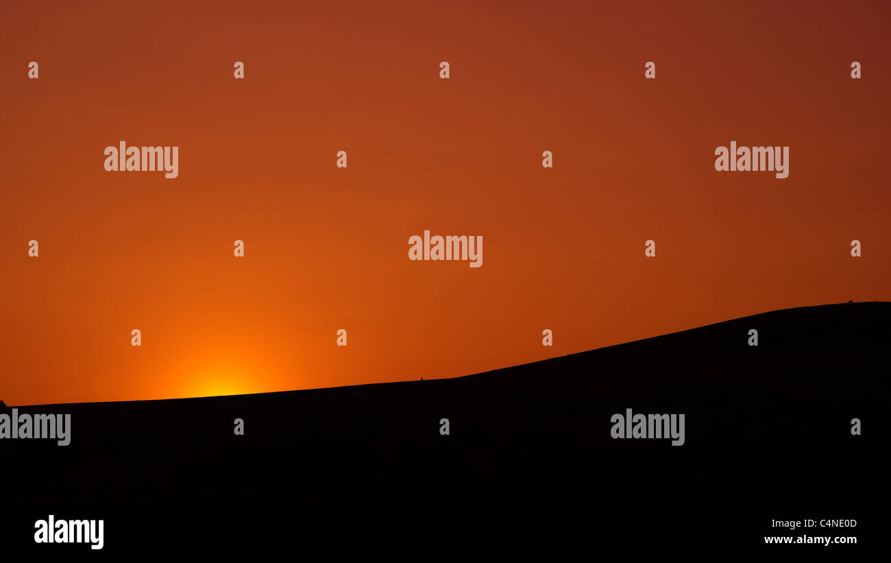 A sunrise breaking over the crest of a silhouetted hill. Picture is in a widescreen, 16:9 aspect ratio. - Stock Image