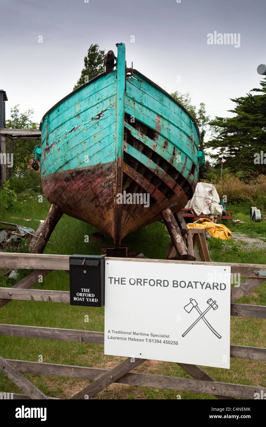 A  wooden boat being repaired at the Orford boatyard, Orford village Suffolk UK - Stock Image