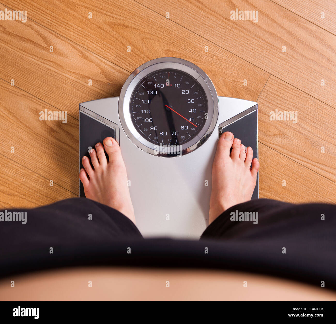 Athletic young girl measuring her weight on a scale - Stock Image
