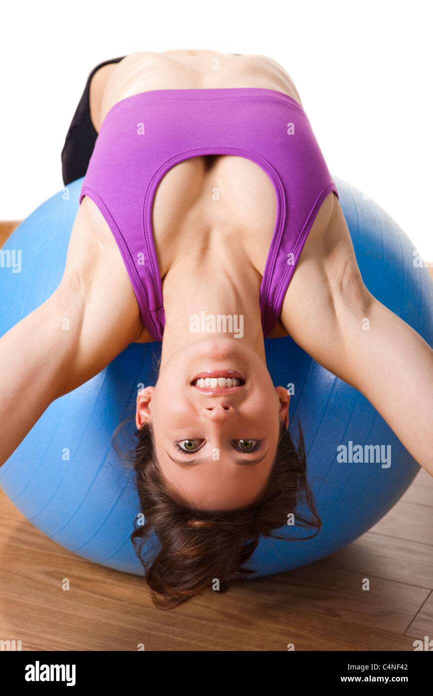 Beautiful young and athletic woman making exercises on a fitness ball - Stock Image