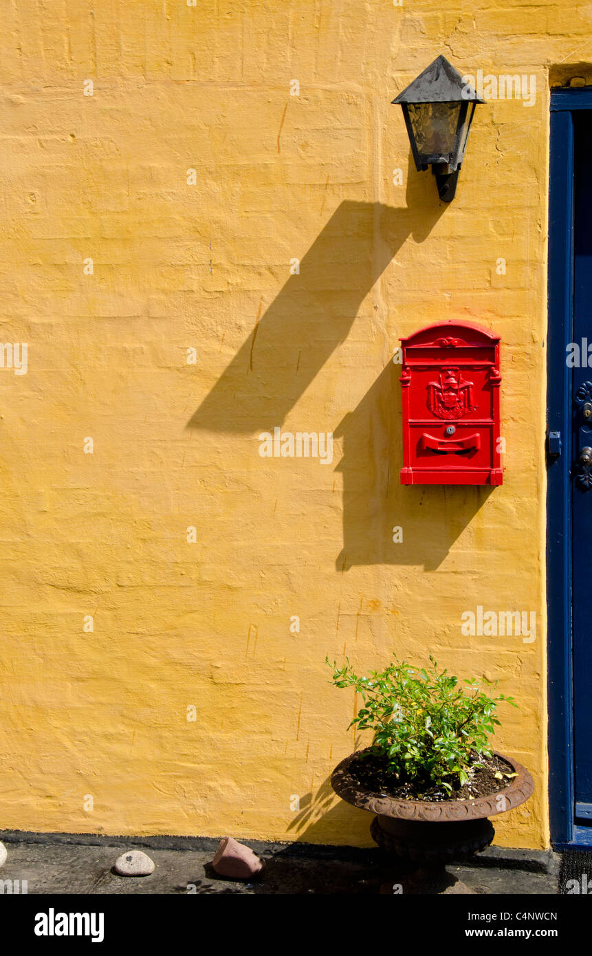 Denmark, Island of Bornholm, Gudhjem. Colorful home in downtown Gudhjem with red post box. - Stock Image