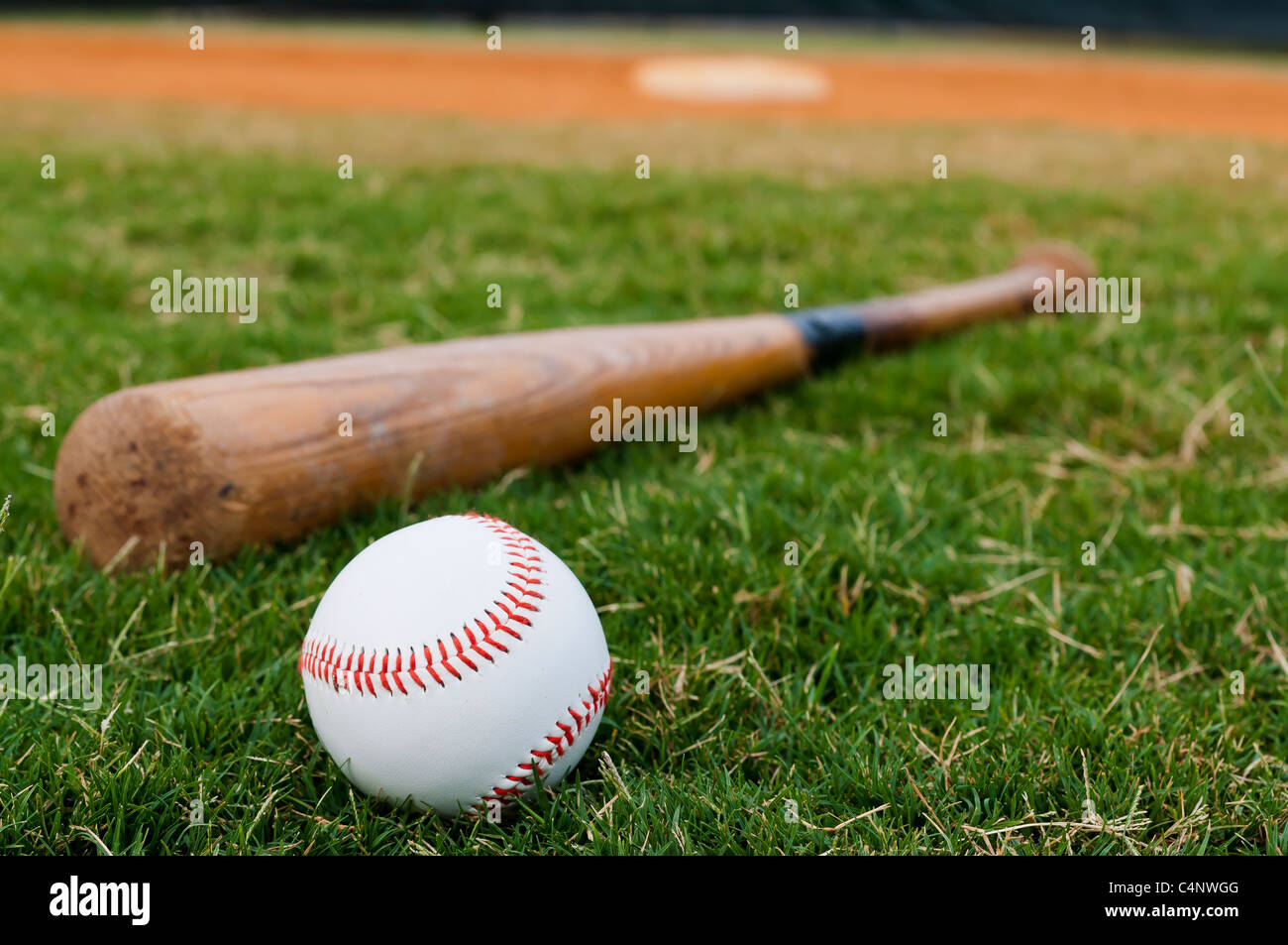 Baseball and bat on field with base and outfield in background. - Stock Image