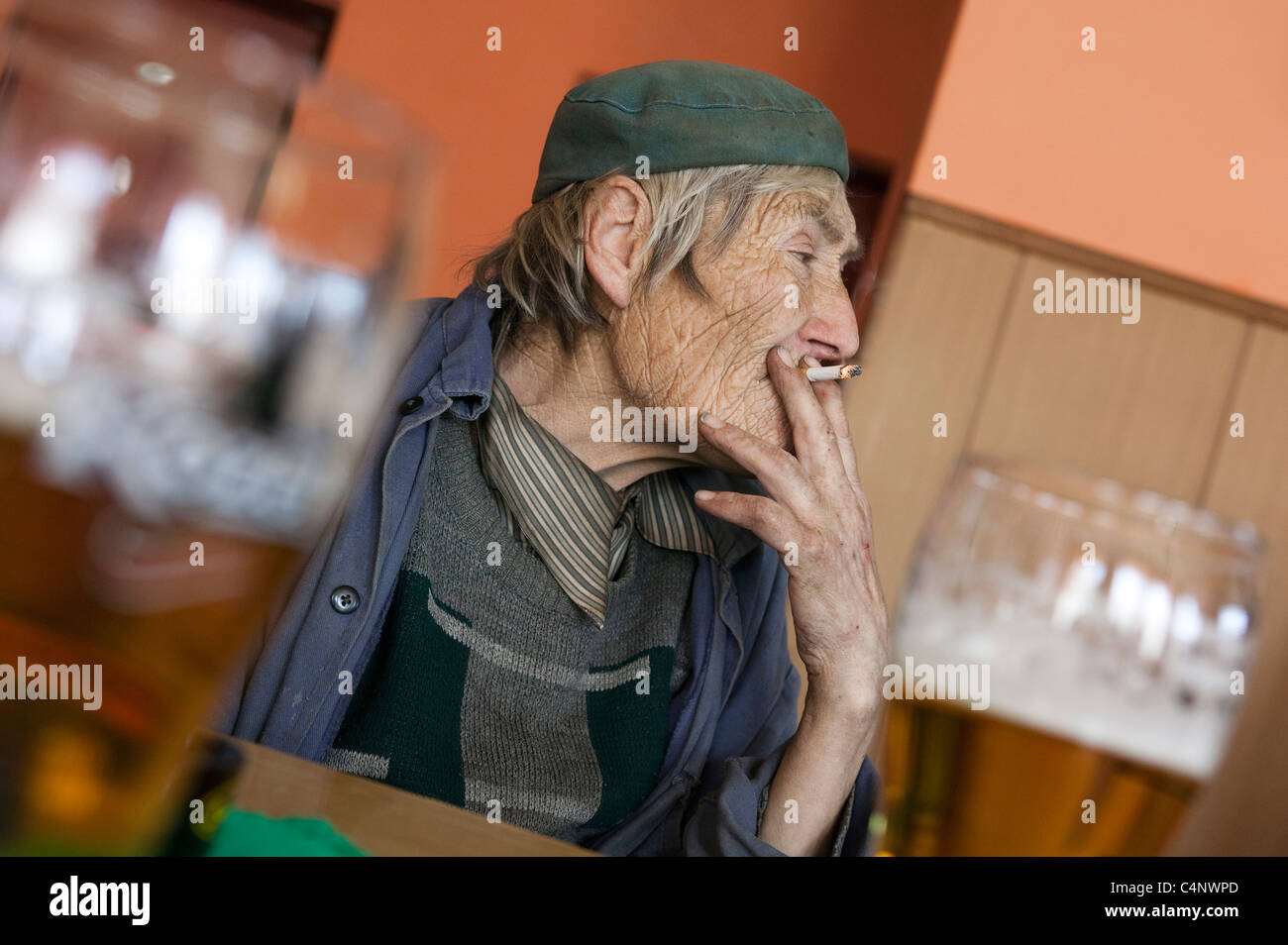 A man having a beer and cigarette in a pub in slovakia - Stock Image