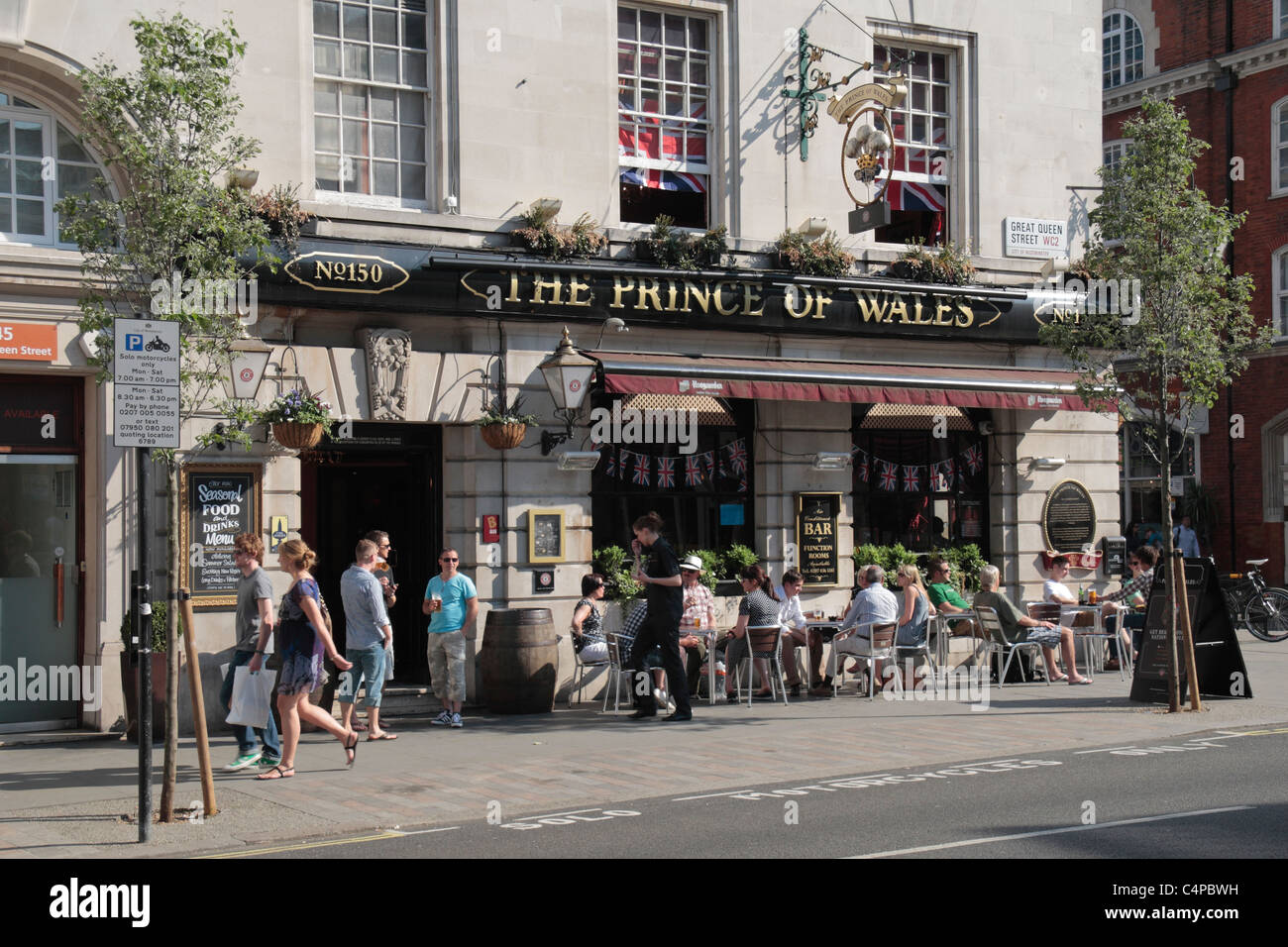 People have an afternoon drink outside The Prince of Wales public house in St Martins Lane, Covent Garden, London, - Stock Image