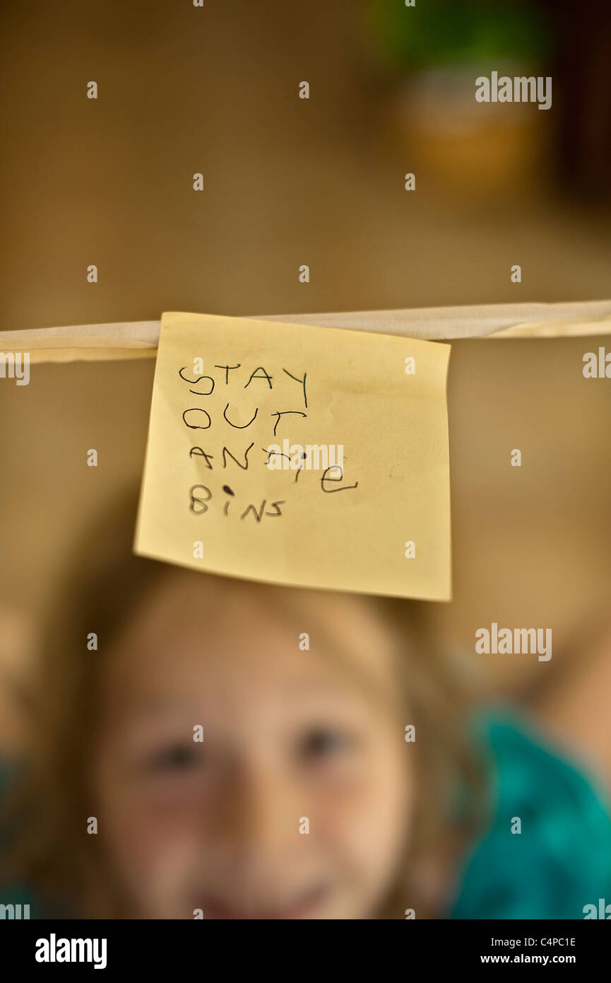 6-year-old girl smiling with sticky note 'Stay Out Antie Bins' - Stock Image