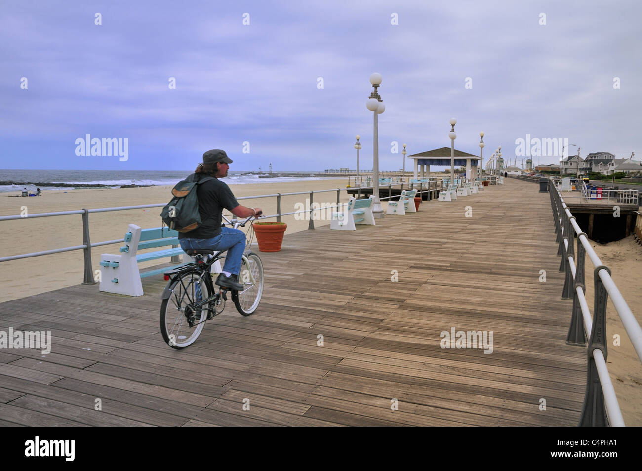 A bicyclist pedals down the boardwalk at Avon-by-the-Sea, New Jersey in spring - Stock Image