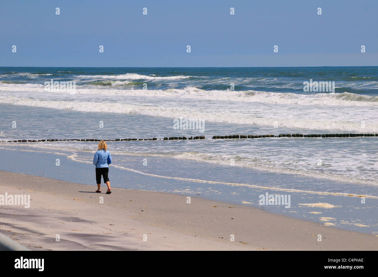 Woman walking on the beach at Brigantine Beach, New Jersey - Stock Image