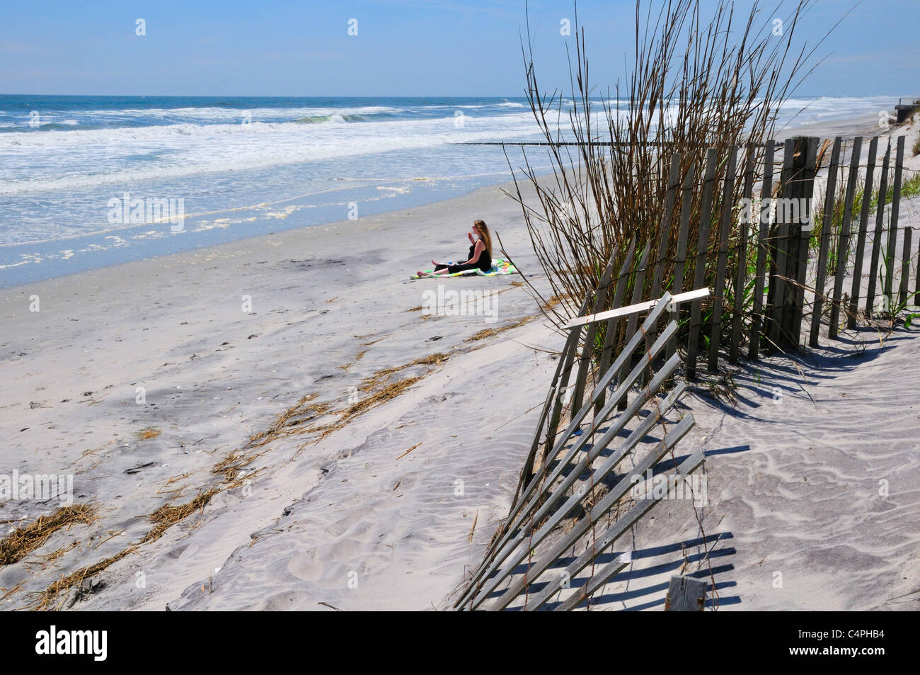 Woman sitting on the beach at Brigantine Beach, New Jersey - Stock Image